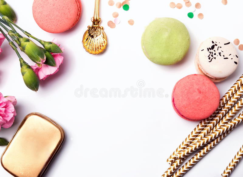Flowers, paper straws, macarons and confetti. On the white background, top view stock image
