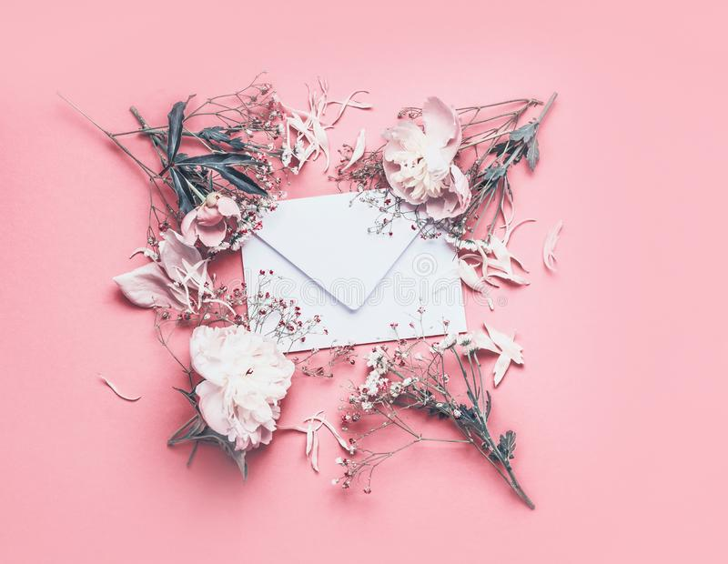 Flowers and petal arrangement around blank envelope on pink background with ribbons, top view. Love feeling letter. Instagram sty. Le. Wedding invitation. Mother royalty free stock image