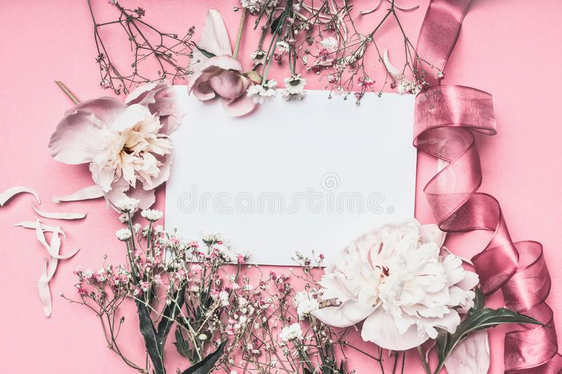 Flowers and petal arrangement around blank paper on pink background with ribbons, top view. Love feeling letter. Instagram style. Wedding invitation. Mother`s stock images