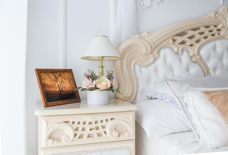 Flowers and photograph on bedside table. In white classic bedroom royalty free stock photos