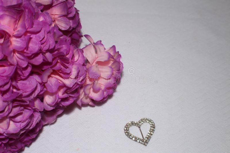 Flowers. Pink flowers and a sliver heart on a white back ground royalty free stock photo
