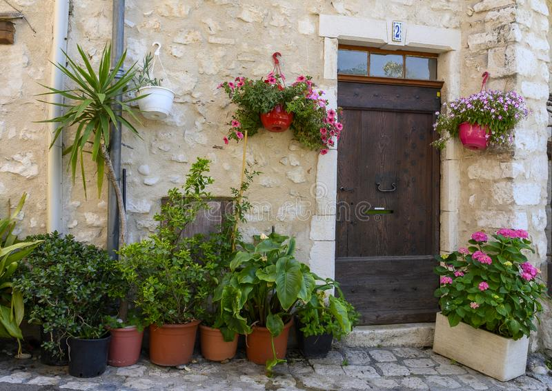 Flowers and plants surround a wooden residence door in Saint Paul-De-Vence, Provence, France royalty free stock images