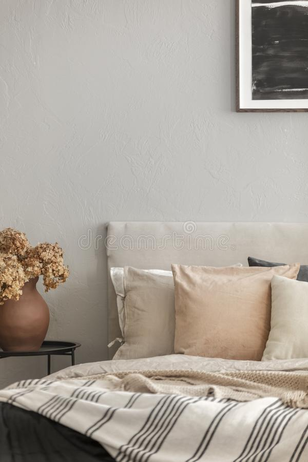 Brown flowers in pottery vase on metal nightstand next to king size bed in scandinavian bedroom interior stock photography