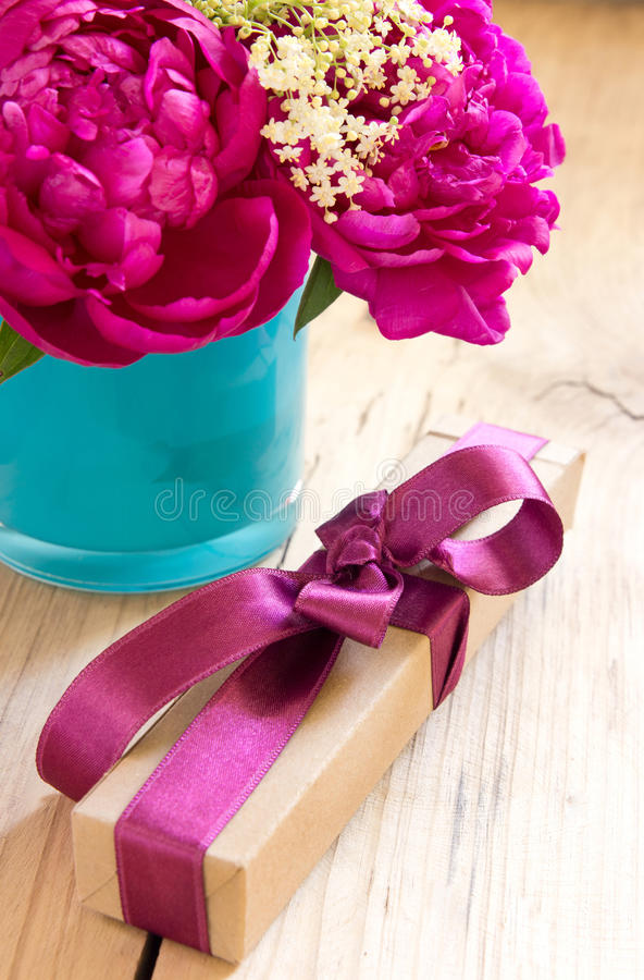 Flowers and present box with ribbon on table,birthday gift. stock images