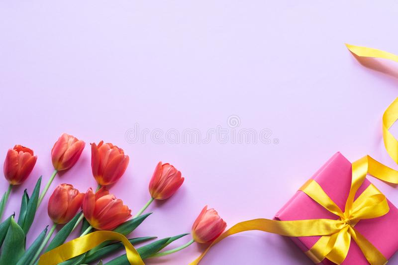 Flowers and red gift box on pink background. Copy space. royalty free stock images