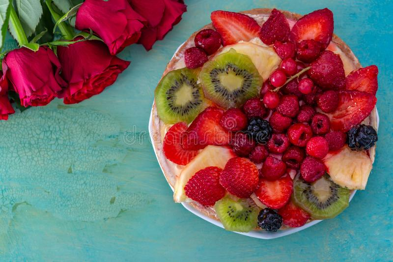 Flowers roses and beautiful delicious sweet cake with berries on a green background. royalty free stock image