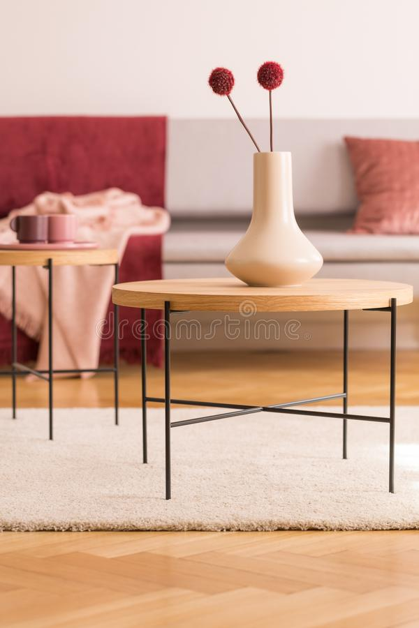 Flowers on round table on white rug in living room interior with wooden floor. Real photo. Concept photo stock photo
