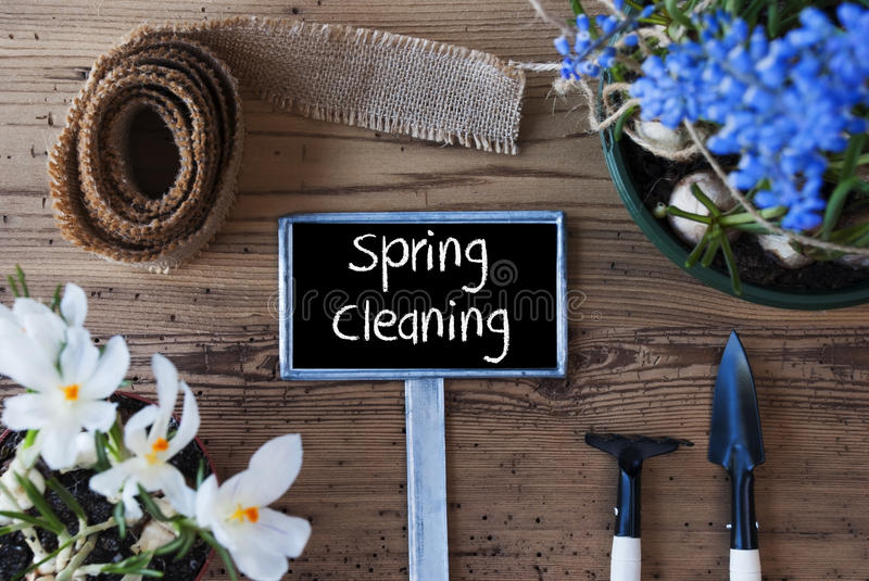 Flowers, Sign, Text Spring Cleaning. Sign With English Text Spring Cleaning. Spring Flowers Like Grape Hyacinth And Crocus. Gardening Tools Like Rake And Shovel royalty free stock images