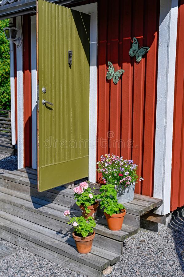 Flowers on stairs infront of a red wooden cabin. In Sweden royalty free stock photography