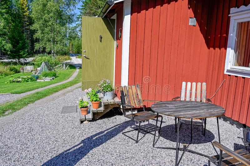 Flowers on stairs infront of a red wooden cabin. In Sweden royalty free stock image