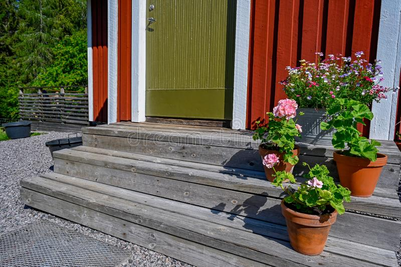 Flowers on stairs infront of a red wooden cabin. In Sweden stock photos