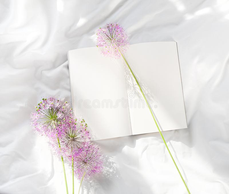 Flowers staying on open book in bed. Romantic good morning. Top view. Flowers staying on open book in white bed. Good morning. Top view stock image
