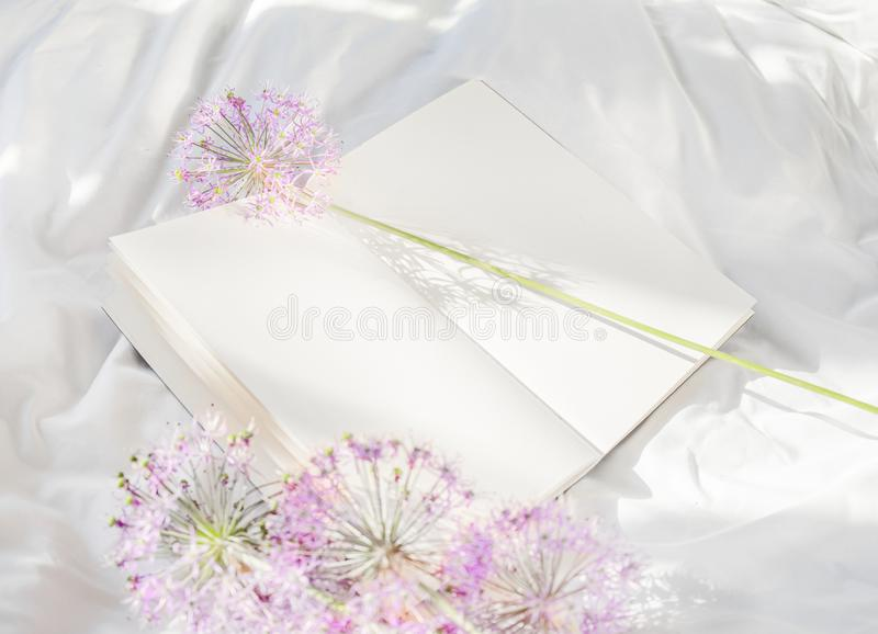 Flowers staying on open book in bed. Romantic good morning. Top view. Flowers staying on open book in white bed. Good morning. Top view royalty free stock photography