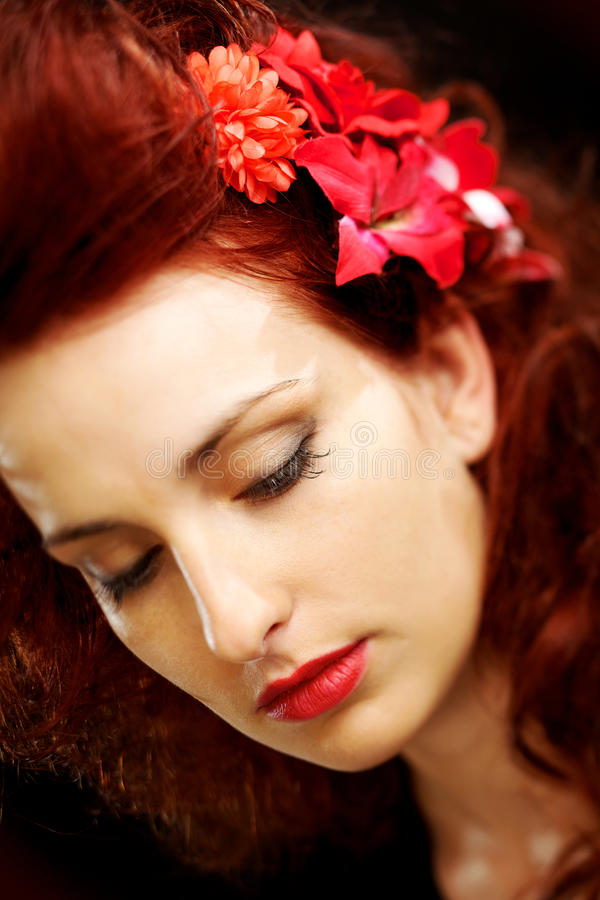 Flowers in striking red hair. Beautiful woman on dark background with flowers in her vivid red hair. Shallow depth of field and focus on the eyes royalty free stock images