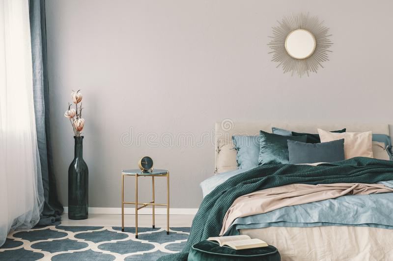 Flowers in stylish bottle like vase next to trendy nightstand with clock in beautiful bedroom interior with beige and emerald royalty free stock images