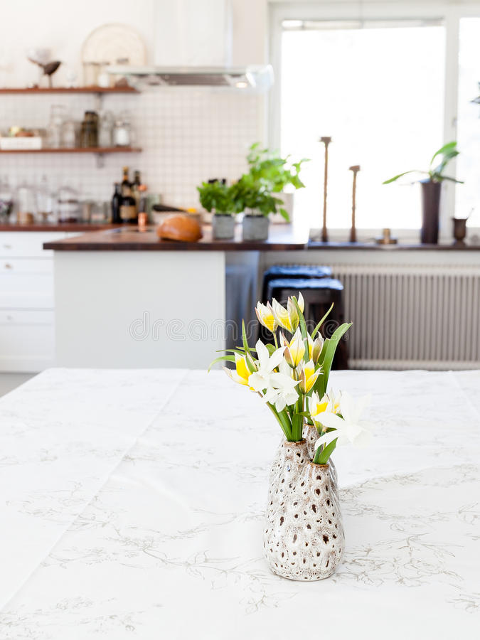 Flowers at the table in the foreground kitchen blurred in the background royalty free stock images