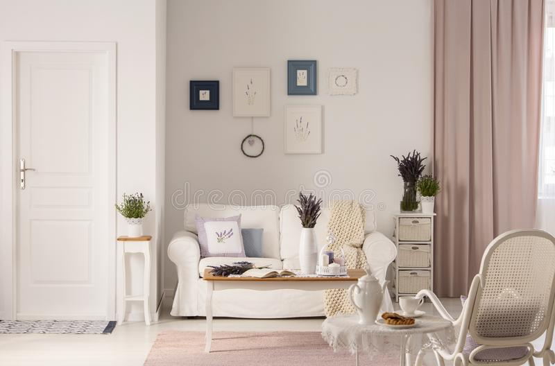 Flowers on table in front of white sofa in pink living room interior with door and armchair. Real photo royalty free stock photos