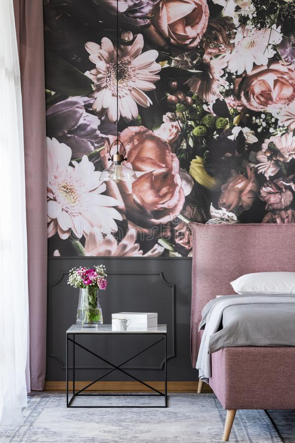 Flowers on table next to pink bed in bedroom interior with patterned wallpaper. Real photo. Concept stock photography