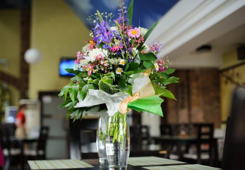 Flowers on table in restaurant. Wedding, decor, decoration, dining, elegant, arrangement, glass, celebration, party, reception, dinner, catering, romance stock photo
