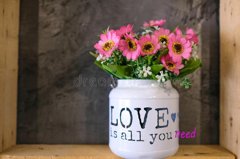 flowers in a tin bucket with a phrase & x22; Love is all You Need& x22; royalty free stock image