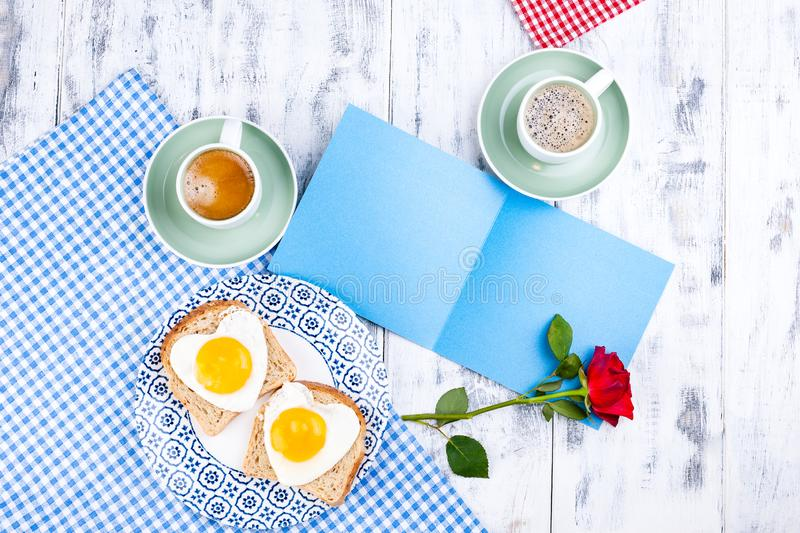 Flowers, Two cups of aromatic coffee and heart-shaped toasts for a romantic morning of lovers. Red rose, letter or note on the. Table. The concept of Valentine` royalty free stock photography