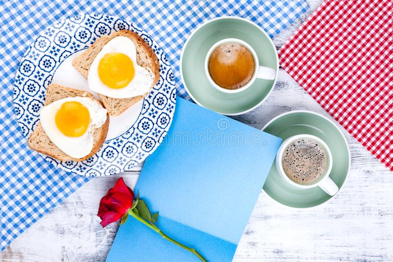 Flowers, Two cups of aromatic coffee and heart-shaped toasts for a romantic morning of lovers. Red rose, letter or note on the. Table. The concept of Valentine` royalty free stock photos