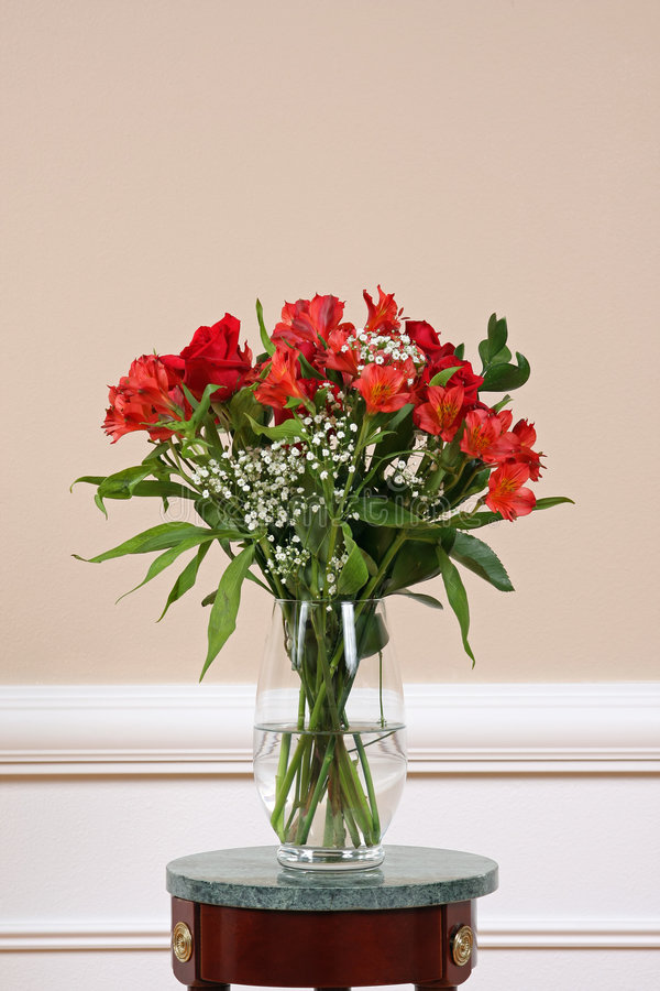Flowers in Vase. Roses and Alstroemeria on a marble stand in a crystal vase royalty free stock photos