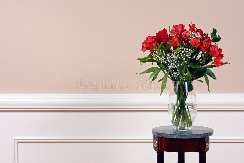 Flowers in Vase. Roses and Alstroemeria on a marble stand in a crystal vase stock photo