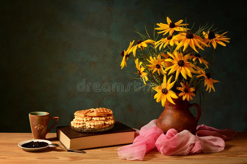 Flowers in a vase, books and cakes royalty free stock photo