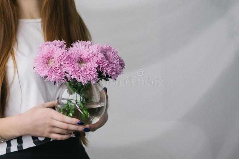 Download Flowers In A Vase In The Hands Of A Girl. A Girl Is Holding