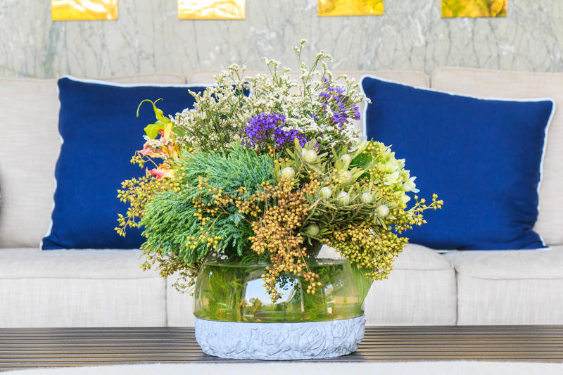 Flowers in the vase on the table in front of the sofa. royalty free stock images
