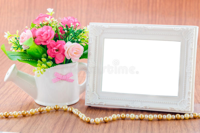 Flowers vase and vintage white picture frame on wooden desktop. royalty free stock photography