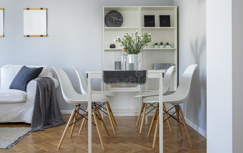 Flowers on white dining table with four trendy chairs in stylish living room stock image