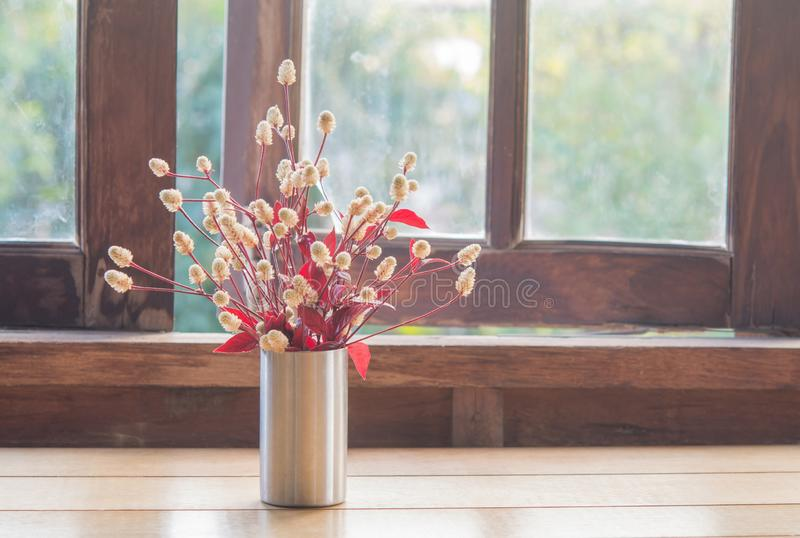 Flowers in a vase and wood window. In the house royalty free stock photography