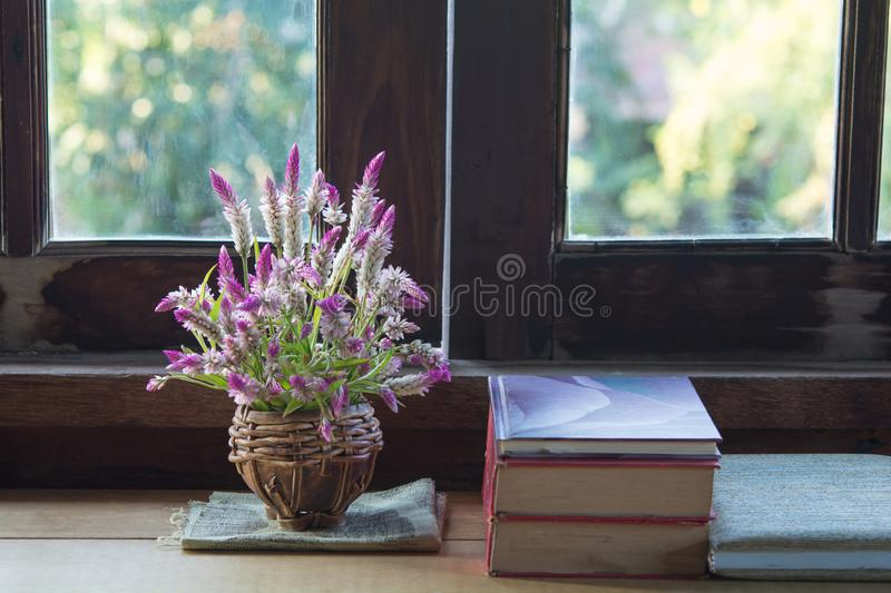 Flowers in a vase and wood window. In the house stock image