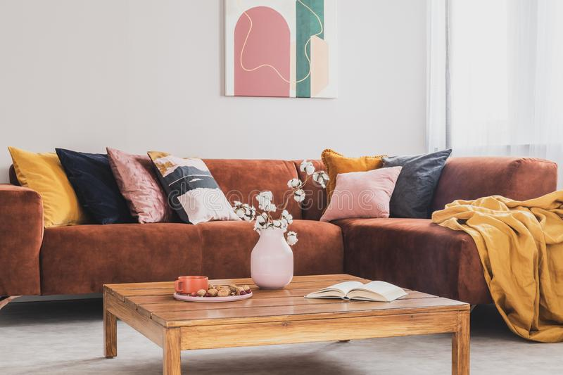 Flowers in vase on wooden coffee table in fashionable living room interior with brown corner sofa with pillows and abstract stock images
