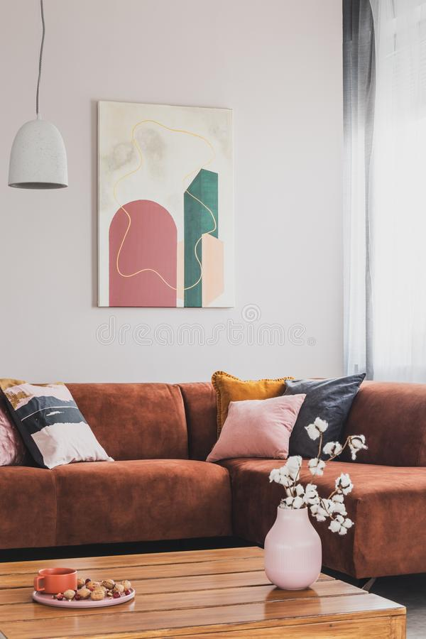Flowers in vase on wooden coffee table in fashionable living room interior with brown corner sofa with pillows and abstract stock photo