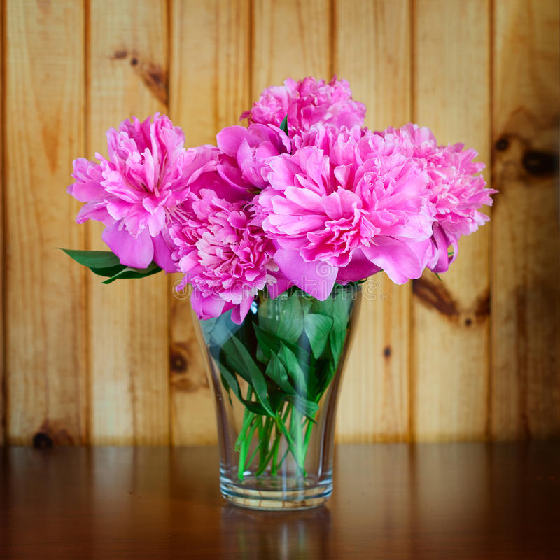 Flowers in a vase on wooden table old stock image
