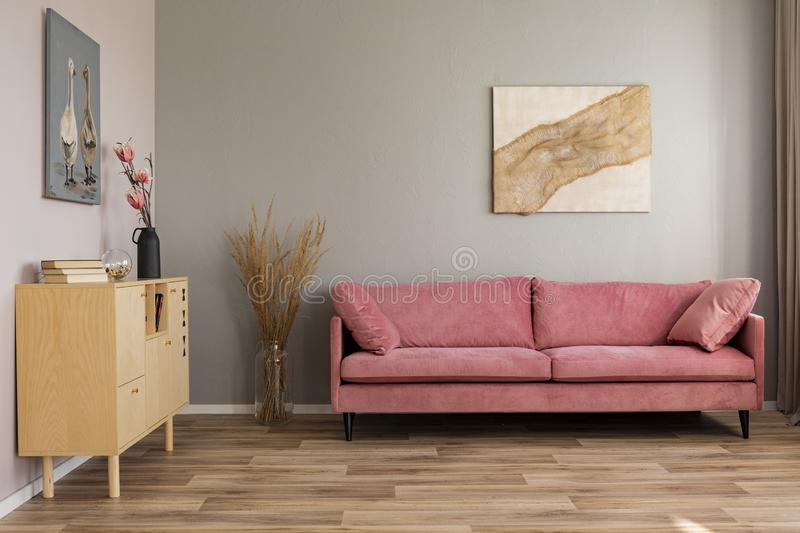 Flowers in vases on wooden commode in contemporary living room interior with pastel pink sofa. Flowers in vases on commode in contemporary living room interior stock photography