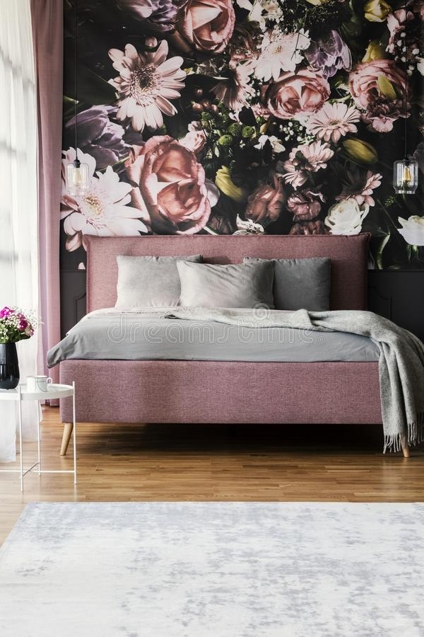 Flowers wallpaper in feminine pink bedroom interior with grey pi. Llows on bed. Real photo concept stock images