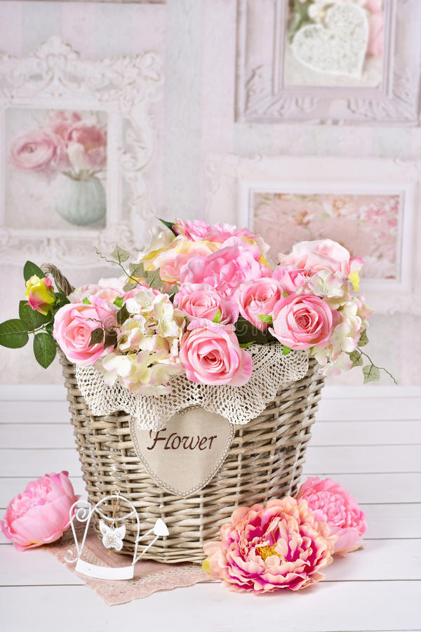 Flowers in wicker basket in vintage style interior. Beautiful romantic flower decoration with pink roses and peonies in wicker basket in vintage style interior royalty free stock photos