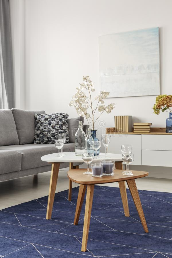 Flowers on wooden coffee table in fashionable living room interior with scandinavian design. Flowers on wooden coffee table in fashionable living room interior stock images