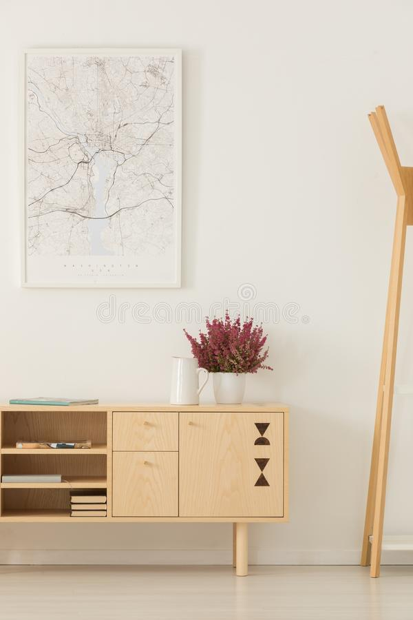 Flowers on wooden cupboard next to rack in white hall interior with poster on the wall stock photography