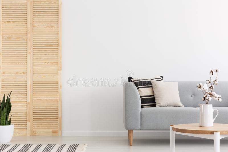 Grey couch with pillows in white flat interior with plant. Real photo. Flowers on wooden table in front of grey couch with pillows in white flat interior with stock photo