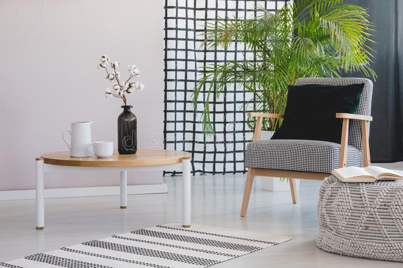 Flowers on wooden table next to armchair in living room interior with plant and pouf. Real photo stock illustration