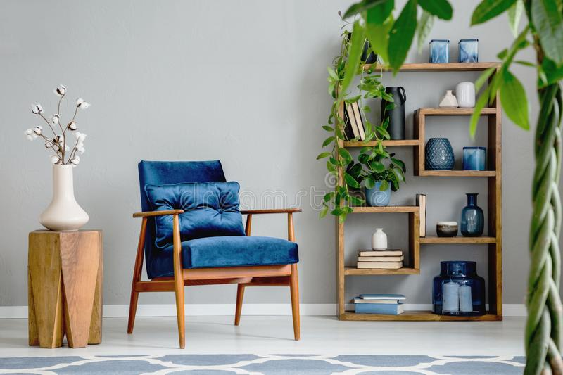 Flowers on wooden table next to blue armchair in grey living room interior with plants. Real photo. Concept stock photos