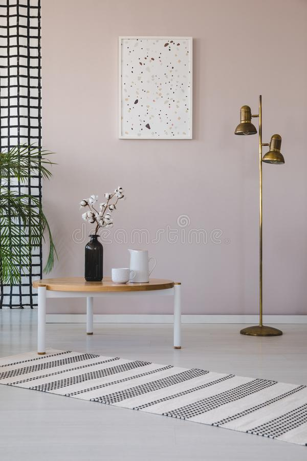 Flowers on wooden table next to gold lamp in living room interior with poster and rug. Real photo.  royalty free illustration
