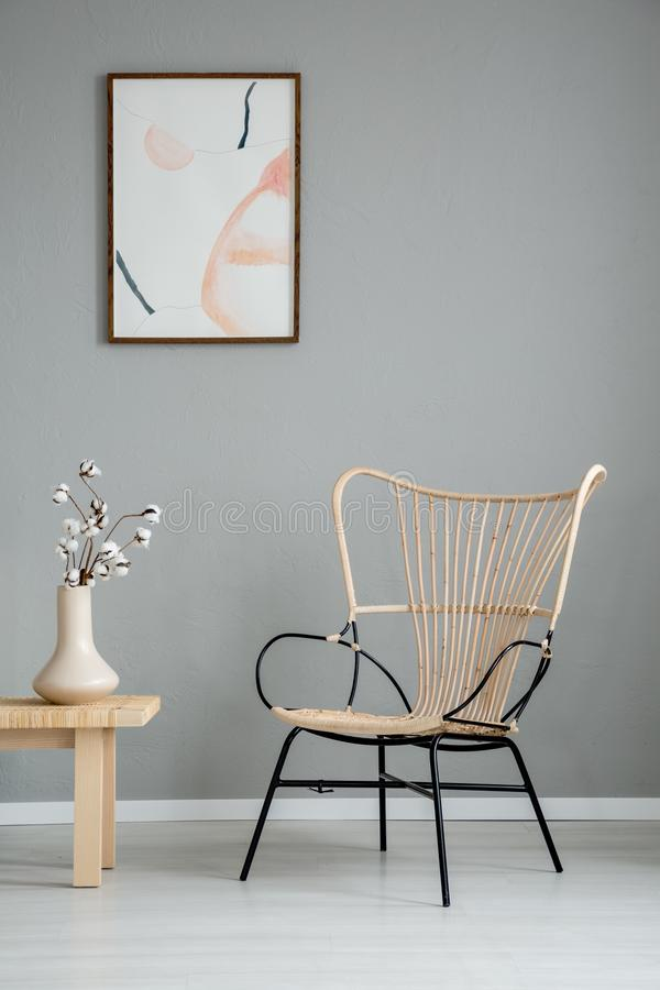 Flowers on wooden table next to modern armchair in grey apartment interior with poster. Real photo stock image
