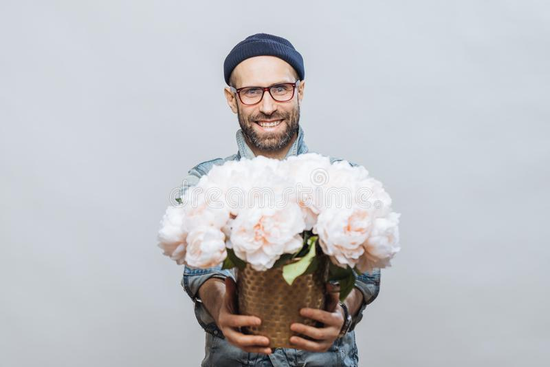 These flowers are for you! Glad smiling bearded male stretches hands while holds bunch of white beautiful flowers, makes present f stock photo