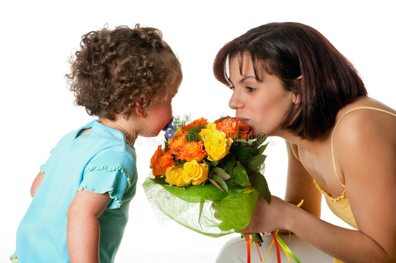 Flowers from the youngest. Toddler girl giving flowers to her mom on mother's day stock photo